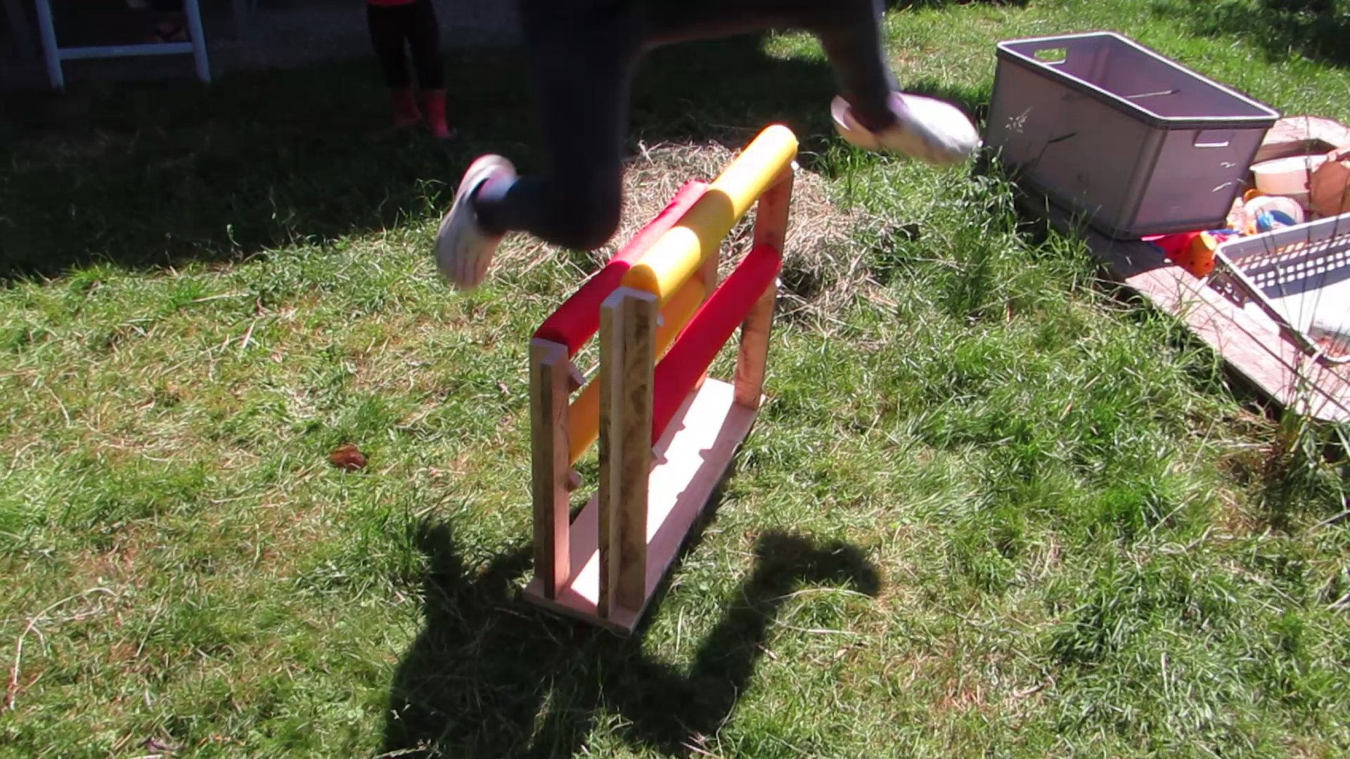 Kid jumps over garden obstacle.