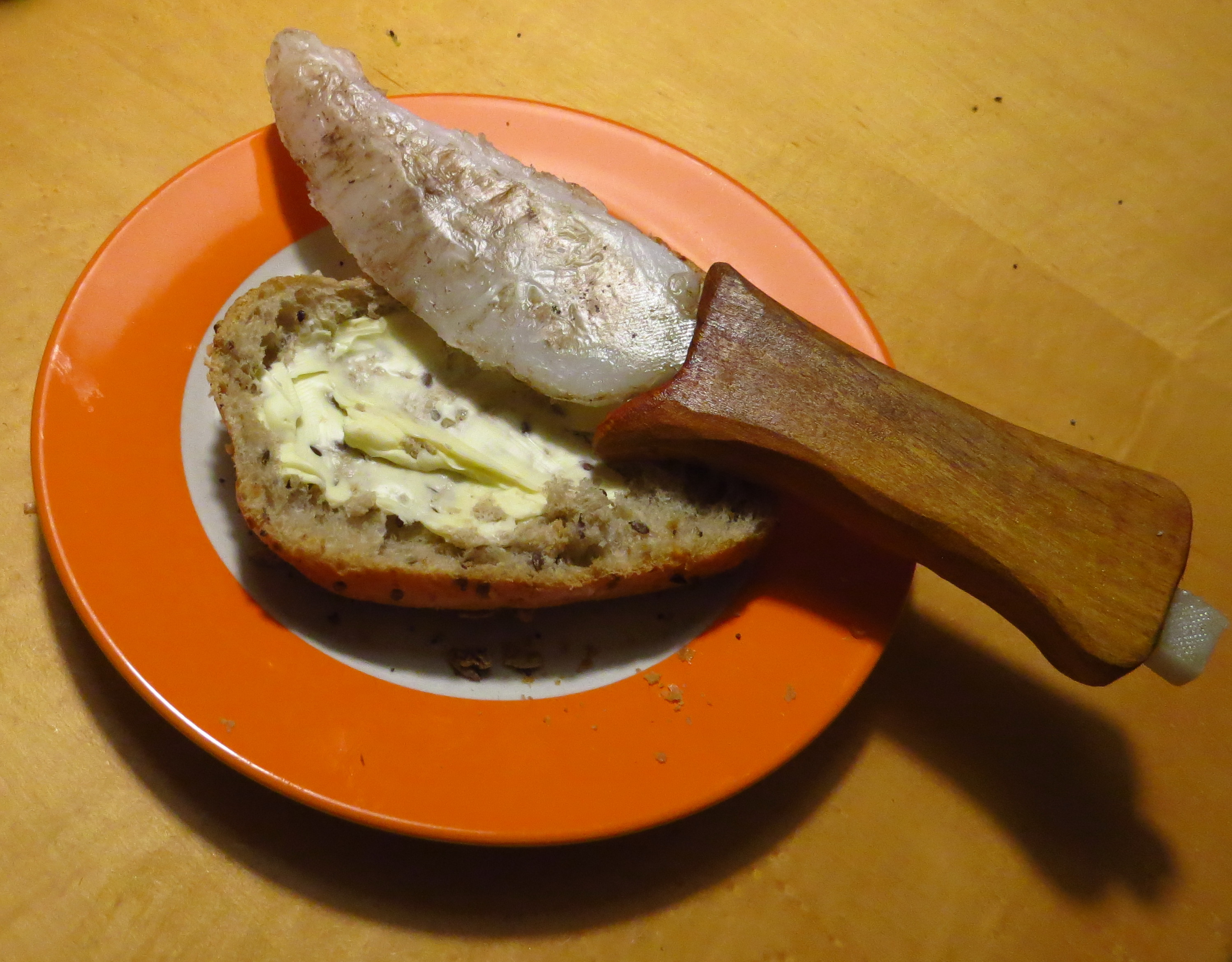 A plastic knife modelling in front of a buttered bun.